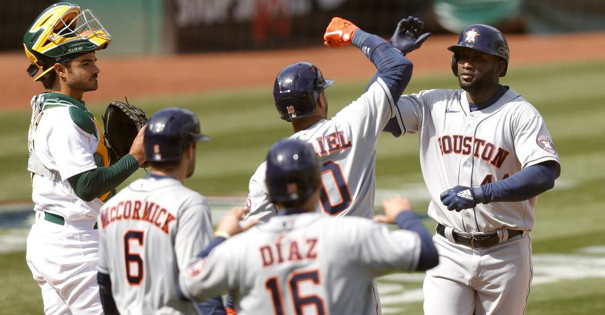Yordan Alvarez #44 of the Houston Astros is congratulated by Yuli Gurriel #10 after he hit a three-run home run in the fifth inning against the Oakland Athletics at RingCentral Coliseum on April 03, 2021 in Oakland, California. (Photo by Ezra Shaw/Getty Images)