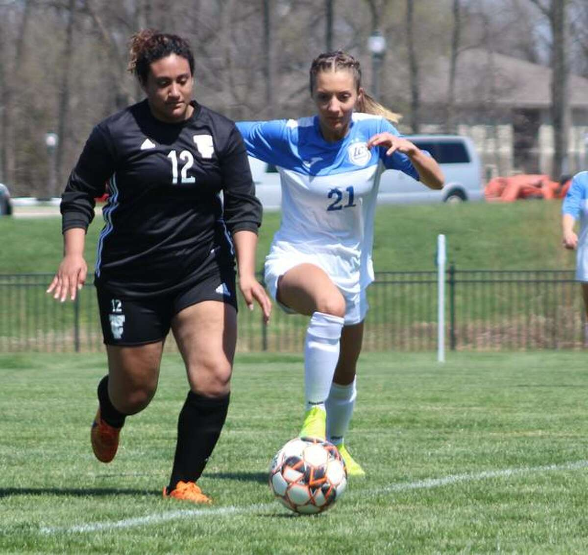 LCCC's Skylar Nickel (5) , a freshman from Carlinville, races for the ball with Triton's Lourdes Moreno (12) in Saturday's season opener at LCCC. The third-ranked Trailblazers downed Triton 5-0.