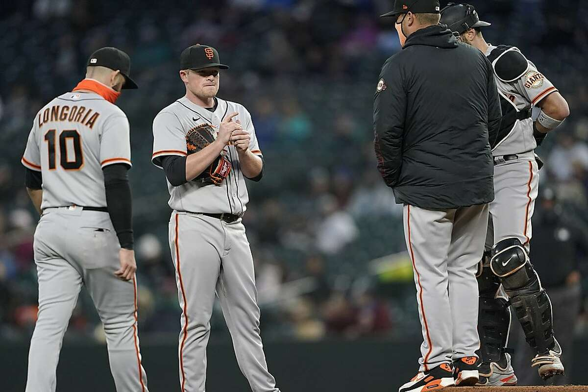 """Giants starting pitcher Logan Webb talks with pitching coach Andrew Bailey, joined by third baseman Evan Longoria and catcher Curt Casali. Webb allowed three runs in 5 ?..."""" innings."""