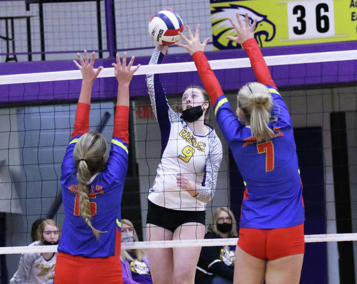 CM's Laura Dunlap (9) hits through the block put up by Roxana's Peyton Petit (7) and Darcey McGuire during the first set Saturday in Bethalto.