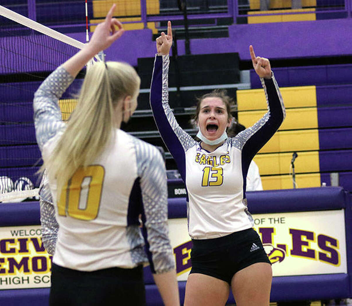 CM's Harper Buhs (13) celebrates a point with teammate Claire Christeson during the Eagles' second-set victory Saturday in Bethalto.