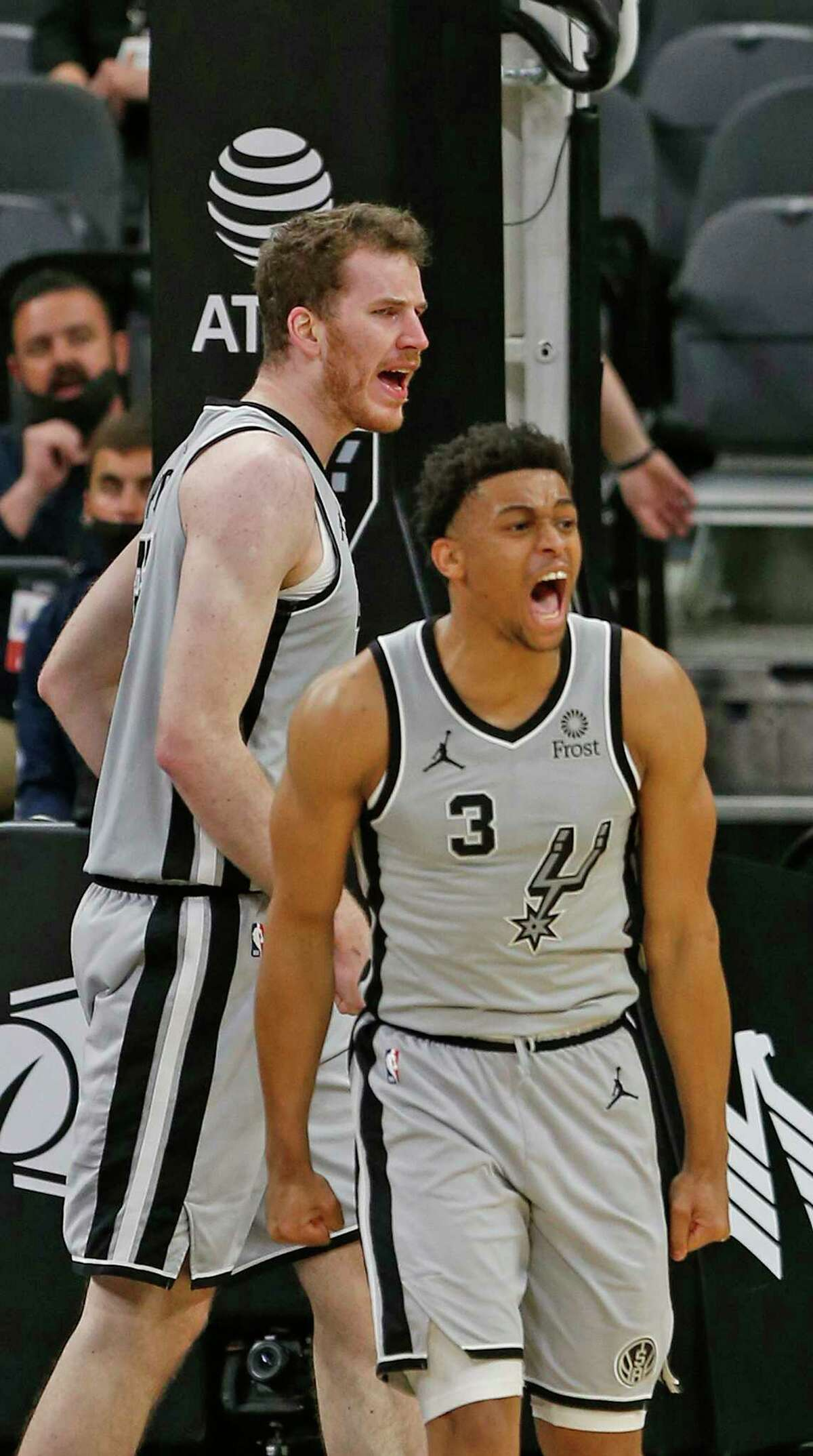 Keldon Johnson #3 of the San Antonio Spurs reacts after a Jakob Poeltl #25,in background against the Indiana Pacers in the first half half on Saturday, April 3, 2021 at the AT&T Center