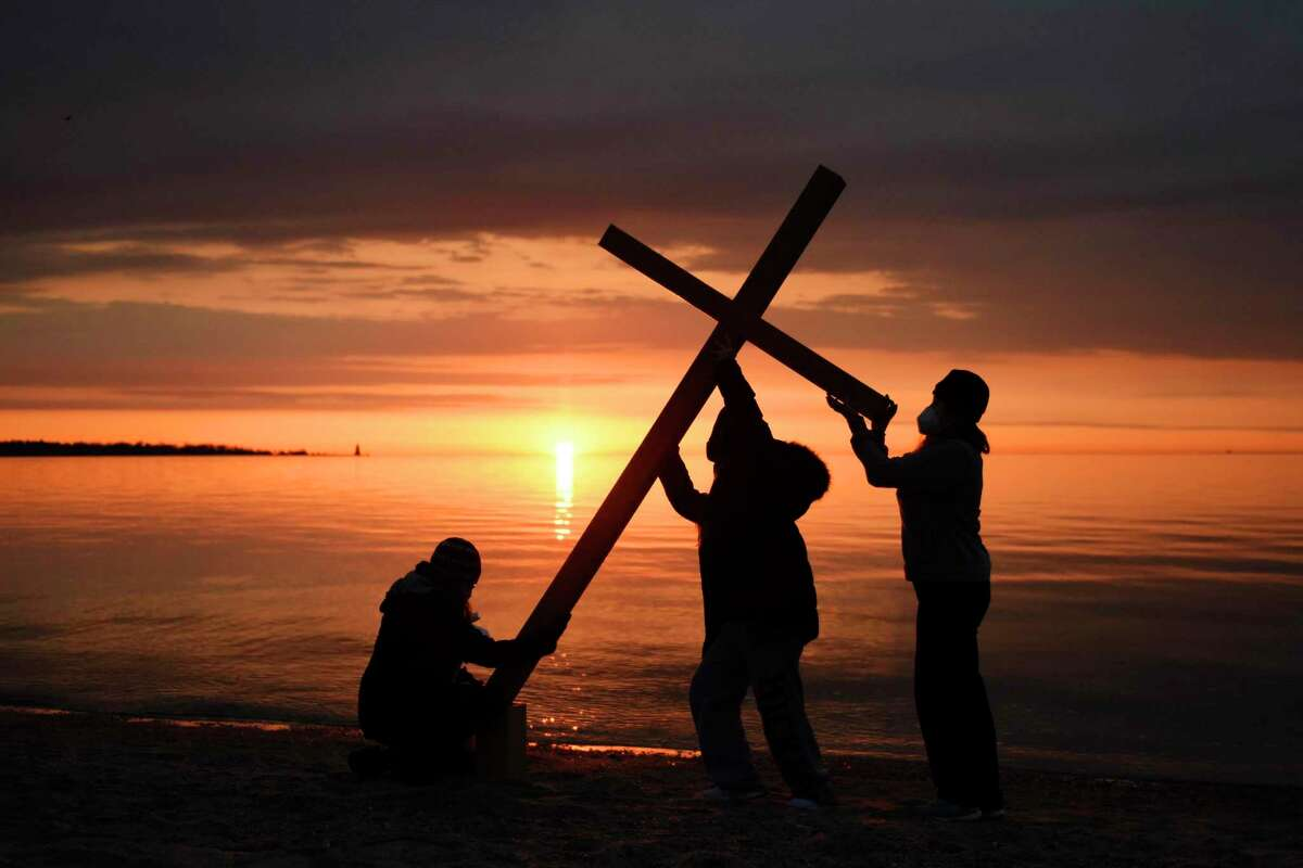 Youth choir members Kelley Alogna, left, Sarah Mickley, center, and Lauren Mickley hoist up the cross on the beach as the sun begins to rise during the Easter Sunrise Beach Service at Greenwich Point Park in Greenwich, Conn. Sunday, April 4, 2021. Presented by First Congregational Church of Greenwich, congregants gathered on the beach to watch the sunrise on a clear Easter morning while worshipping with music from the First Church youth choir and a sermon led by Associate Pastor the Rev. Cydney Van Dyke.