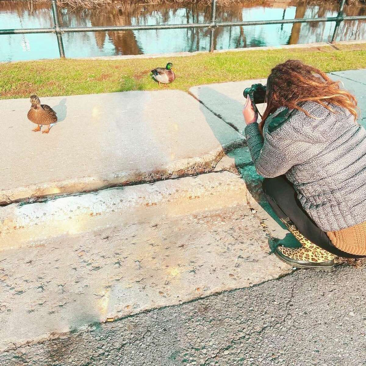 Vaughn is pictured taking a picture of a duck. As well as animals, she enjoys photographing families, nature scenes and more. (Courtesy photo)
