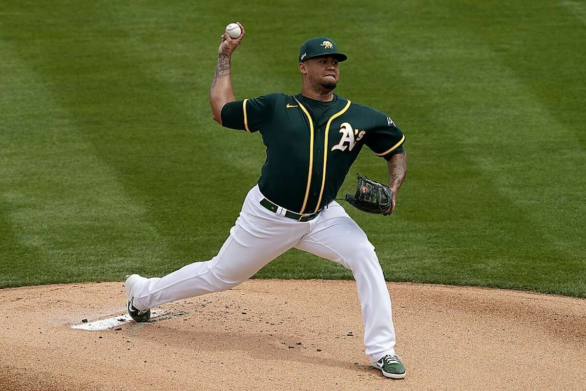 Oakland Athletics starting pitcher Frankie Montas throws agaisnt the Seattle Mariners during the first inning of a spring training baseball game, Thursday, March 25, 2021, in Mesa, Ariz. (AP Photo/Matt York)