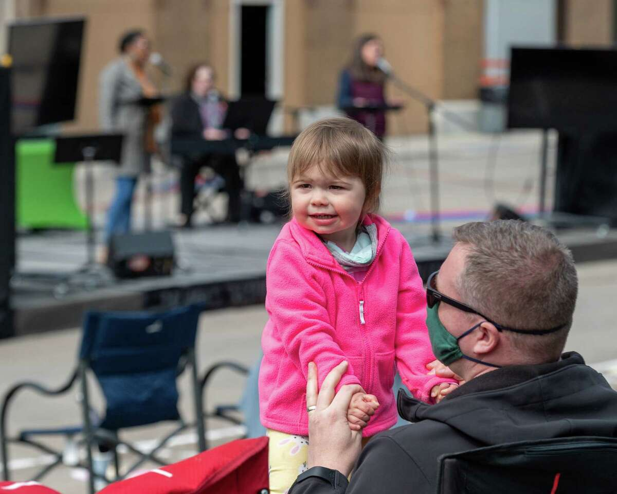 Scarlett Kampschaefer dances on the knee of her father Jason as the band plays during an Easter service by Christ's Church of Albany at the Washington Park Amphitheater in Albany, NY, on Sunday, April 4. (Jim Franco/Special to the Times Union)