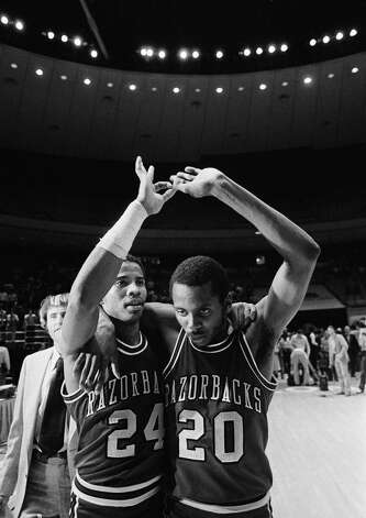 Two tired Arkansas teammates, guard U.S. Reed (24) and guard Darrell Walker (20) embrace and raise their arms in victory after Reed sank a final-second shot from mid-court to beat Louisville, 74-73, in the second round of the NCAA tournament in Austin on Saturday, March 15, 1981. Walker, who returned to the starting lineup after an 11 game absence, led Arkansas scoring with 23 points in the stunning victory. (AP Photo/PBL Photo: PBL/AP / 1981 AP