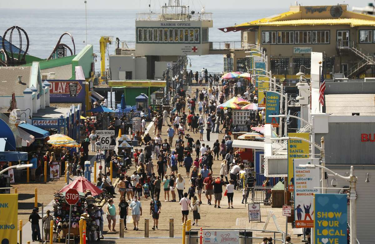 A number of people visiting the Santa Monica Pier ebbs and flows as people take advantage of the warm weather during spring break in Southern California on Monday, Mar. 29, 2021.