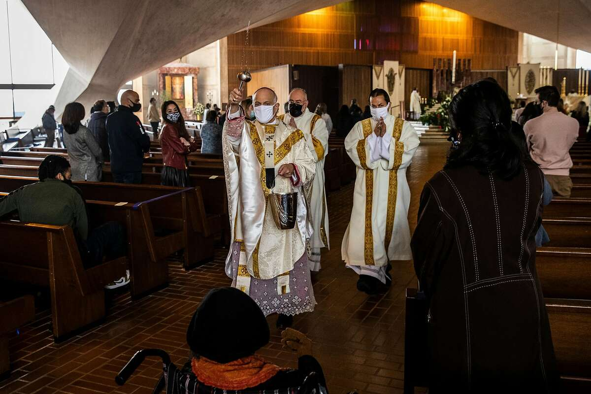 Archbishop Salvatore Cordileone sprinkles holy water onto attendees during an in-church Easter Mass.
