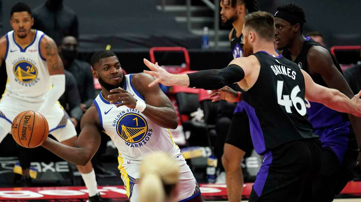 Golden State Warriors forward Eric Paschall (7) passes the ball in front of Toronto Raptors center Aron Baynes (46) during the first half of an NBA basketball game Friday, April 2, 2021, in Tampa, Fla. (AP Photo/Chris O'Meara)