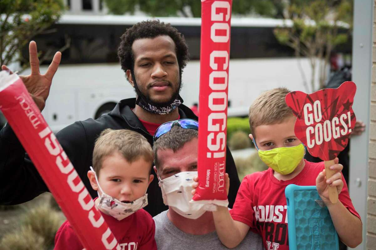 Houston forward Justin Gorham poses for a photo with UH fans Brad Mills and his sons Dylan and Mason as the Cougars basketball team returned to campus from Indianapolis Sunday, April 4, 2021 in Houston, after the Cougars were eliminated from the Final Four Saturday night by Baylor.