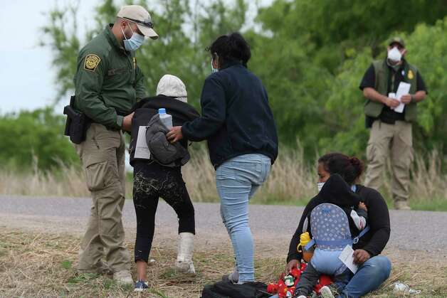 A U.S. Border Patrol agent aids a young migrant with an injured ankle after they were detained west of La Joya, Texas, Friday, April 2, 2021. Photo: Jerry Lara, San Antonio Express-News / **MANDATORY CREDIT FOR PHOTOG AND SAN ANTONIO EXPRESS-NEWS/NO SALES/MAGS OUT/TV   © 2019 San Antonio Express-News