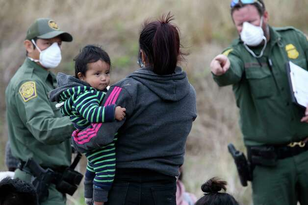 A mother holds her child as U.S. Border Patrol agents wait on transportation west of La Joya, Texas, Friday, April 2, 2021. A group of around 40, mostly Central American migrants, was detained on Military Road. Some in the group were unaccompanied minors. Photo: Jerry Lara, San Antonio Express-News / **MANDATORY CREDIT FOR PHOTOG AND SAN ANTONIO EXPRESS-NEWS/NO SALES/MAGS OUT/TV   © 2019 San Antonio Express-News