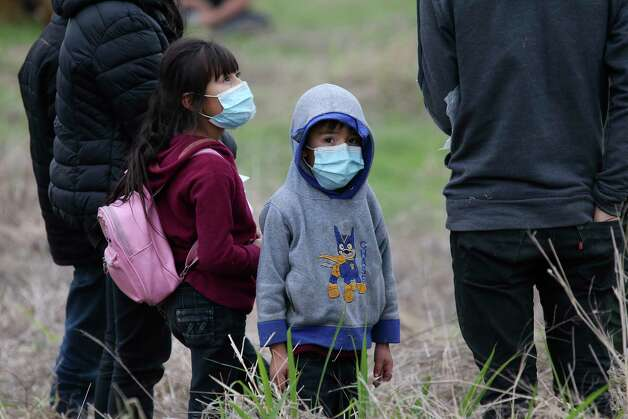A migrant child waits with family after they were detained by U.S. Border Patrol agents aided by Texas Department of Public Safety troops west of La Joya, Texas, Friday, April 2, 2021. A group pf around 40 migrants, some unaccompanied minors, were detain in the area. Photo: Jerry Lara, San Antonio Express-News / **MANDATORY CREDIT FOR PHOTOG AND SAN ANTONIO EXPRESS-NEWS/NO SALES/MAGS OUT/TV   © 2019 San Antonio Express-News