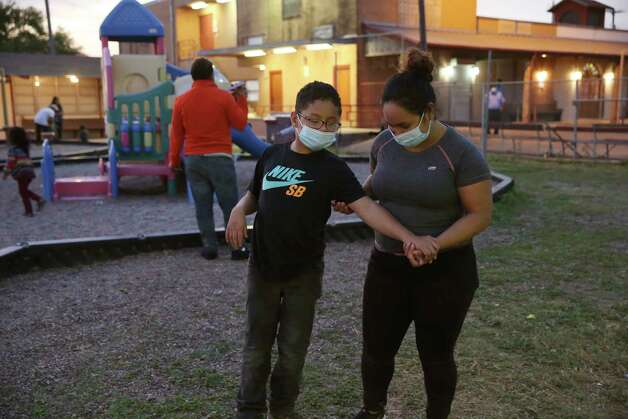 Mari Maldonado helps her son, Erick, 12, as he plays at the Our Lady of Guadalupe Church parish school, Thursday, March 25, 2021. They are migrants from Honduras who had recently been released from U.S. Border Patrol custody. The church has opened its door to house overflow, in keeping with COVID-19 protocols, of migrants from the Catholic Charities of the Rio Grande Valley Respite Center. Photo: Jerry Lara, San Antonio Express-News / **MANDATORY CREDIT FOR PHOTOG AND SAN ANTONIO EXPRESS-NEWS/NO SALES/MAGS OUT/TV   © 2019 San Antonio Express-News