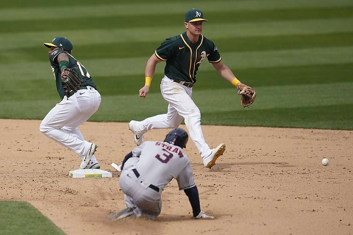 Oakland Athletics shortstop Elvis Andrus, left, cannot field a throwing error by third baseman Matt Chapman, top, as Houston Astros' Myles Straw (3) advances to second base during the sixth inning of a baseball game in Oakland, Calif., Sunday, April 4, 2021.