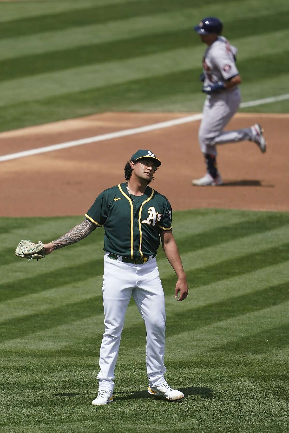 Houston Astros' Jason Castro, top, rounds the bases after hitting a two-run home run off Oakland Athletics pitcher Sean Manaea, bottom, during the second inning of a baseball game in Oakland, Calif., Sunday, April 4, 2021.