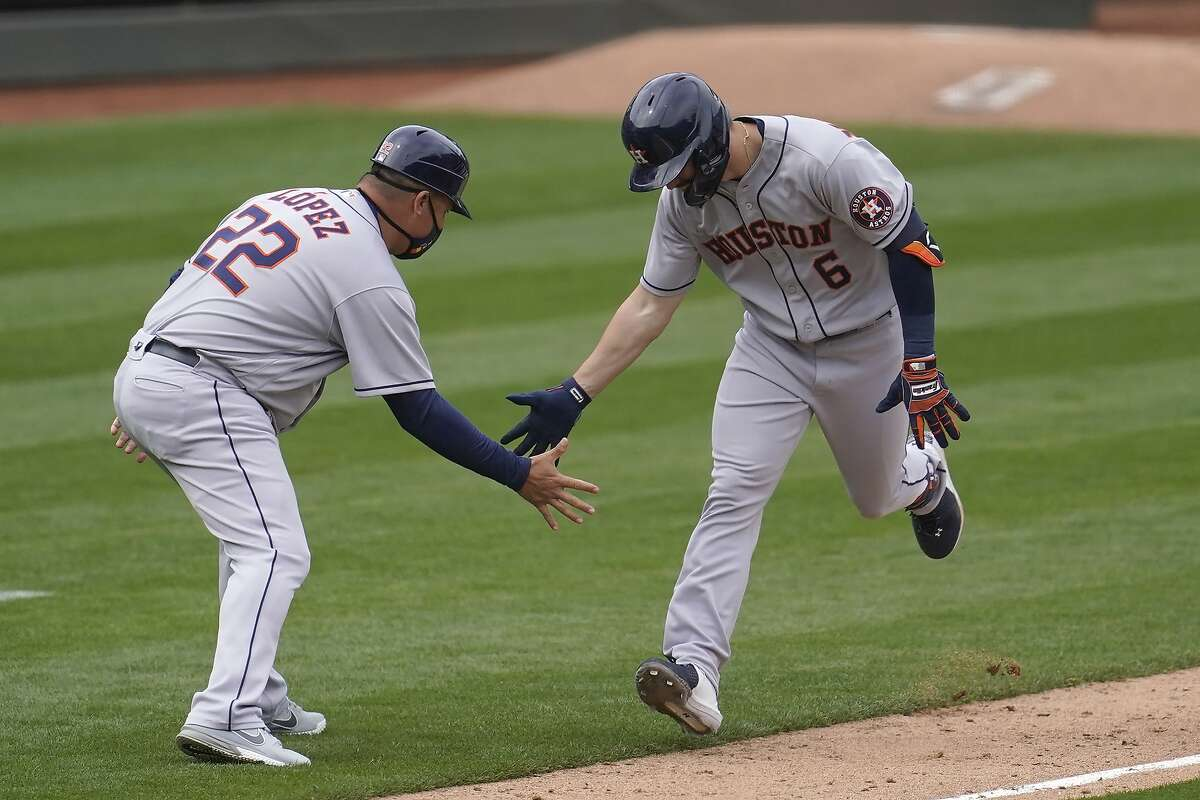 Houston Astros' Chas McCormick (6) is congratulated by third base coach Omar Lopez (22) after hitting a three-run home run against the Oakland Athletics during the sixth inning of a baseball game in Oakland, Calif., Sunday, April 4, 2021.