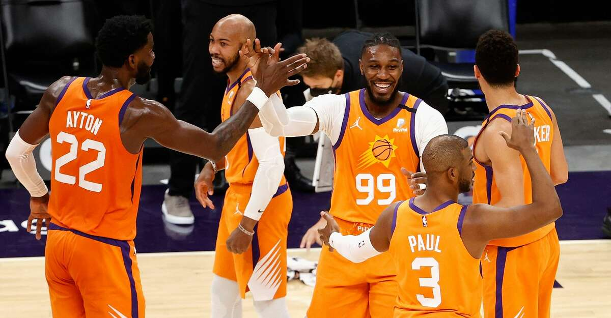 Jae Crowder #99 of the Phoenix Suns high fives Deandre Ayton #22, Chris Paul #3, Devin Booker #1 and Jevon Carter #4 after drawing a foul on a three-point shot during the first half of the NBA game against the Oklahoma City Thunder at Phoenix Suns Arena on April 02, 2021 in Phoenix, Arizona. NOTE TO USER: User expressly acknowledges and agrees that, by downloading and or using this photograph, User is consenting to the terms and conditions of the Getty Images License Agreement. (Photo by Christian Petersen/Getty Images)