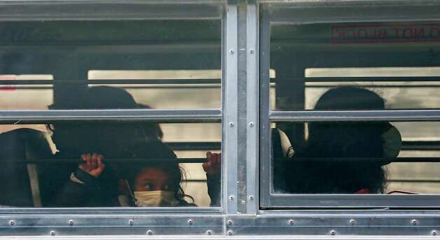 A young girl peers out of a bus carrying migrants to the Brownsville, Texas bus station, Thursday, Feb. 25, 2021. The migrants were released by U.S. Immigration after entering the U.S. by crossing the Rio Grande earlier in the week. Photo: Jerry Lara, San Antonio Express-News / **MANDATORY CREDIT FOR PHOTOG AND SAN ANTONIO EXPRESS-NEWS/NO SALES/MAGS OUT/TV   © 2019 San Antonio Express-News