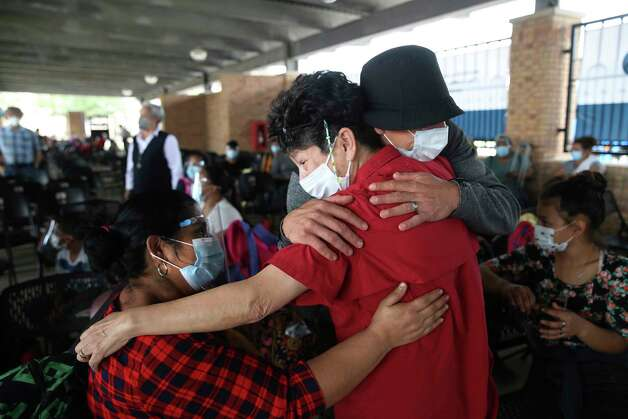Asylum seekers are greeted by a charity volunteer, center, at the Brownsville, Texas bus station, Thursday, Feb. 25, 2021. The group of 27 were the first allowed to enter the U.S. from a migrant camp in Matamoros, Mexico. The camp sprang up when the Trump administration implemented the Migrant Protection Program, which returned migrants back to Mexico to fight their asylum case before U.S. Immigration judges virtually. On Thursday, The Biden administration started allowing the asylum seekers entry into the U.S. Photo: Jerry Lara, San Antonio Express-News / **MANDATORY CREDIT FOR PHOTOG AND SAN ANTONIO EXPRESS-NEWS/NO SALES/MAGS OUT/TV   © 2019 San Antonio Express-News