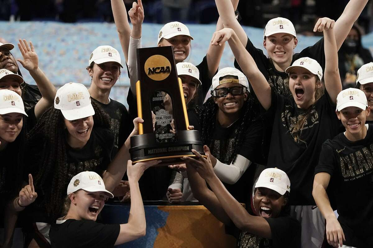 Stanford players celebrate with the trophy after the championship game against Arizona in the women's Final Four NCAA college basketball tournament, Sunday, April 4, 2021, at the Alamodome in San Antonio. Stanford won 54-53. (AP Photo/Morry Gash)