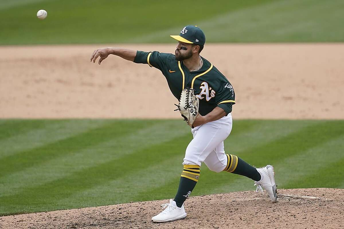 Oakland Athletics' Ka'ai Tom pitches to a Houston Astros batter during the ninth inning of a baseball game in Oakland, Calif., Sunday, April 4, 2021. (AP Photo/Jeff Chiu)