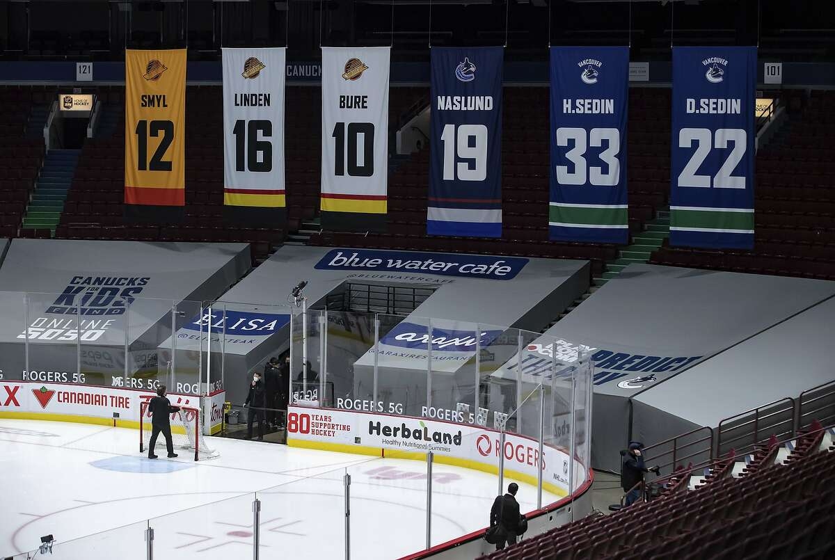 The net is removed from the ice after Vancouver's home game against the Calgary Flames on Wednesday was postponed.