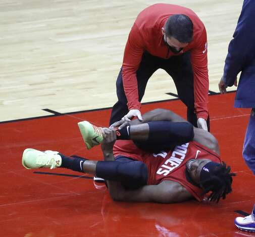 Houston Rockets forward Danuel House Jr. (4) lies on the ground grabbing his right ankle after falling to the floor during the first half of an NBA basketball game at Toyota Center, Sunday, April 4, 2021. Photo: Karen Warren/Staff Photographer / @2021 Houston Chronicle