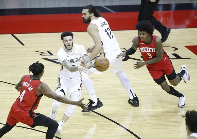 New Orleans Pelicans guard Lonzo Ball (2) passes the ball between Houston Rockets forward Danuel House Jr. (4) and guard Kevin Porter Jr. (3) during the first half of an NBA basketball game at Toyota Center, Sunday, April 4, 2021. Photo: Karen Warren/Staff Photographer / @2021 Houston Chronicle