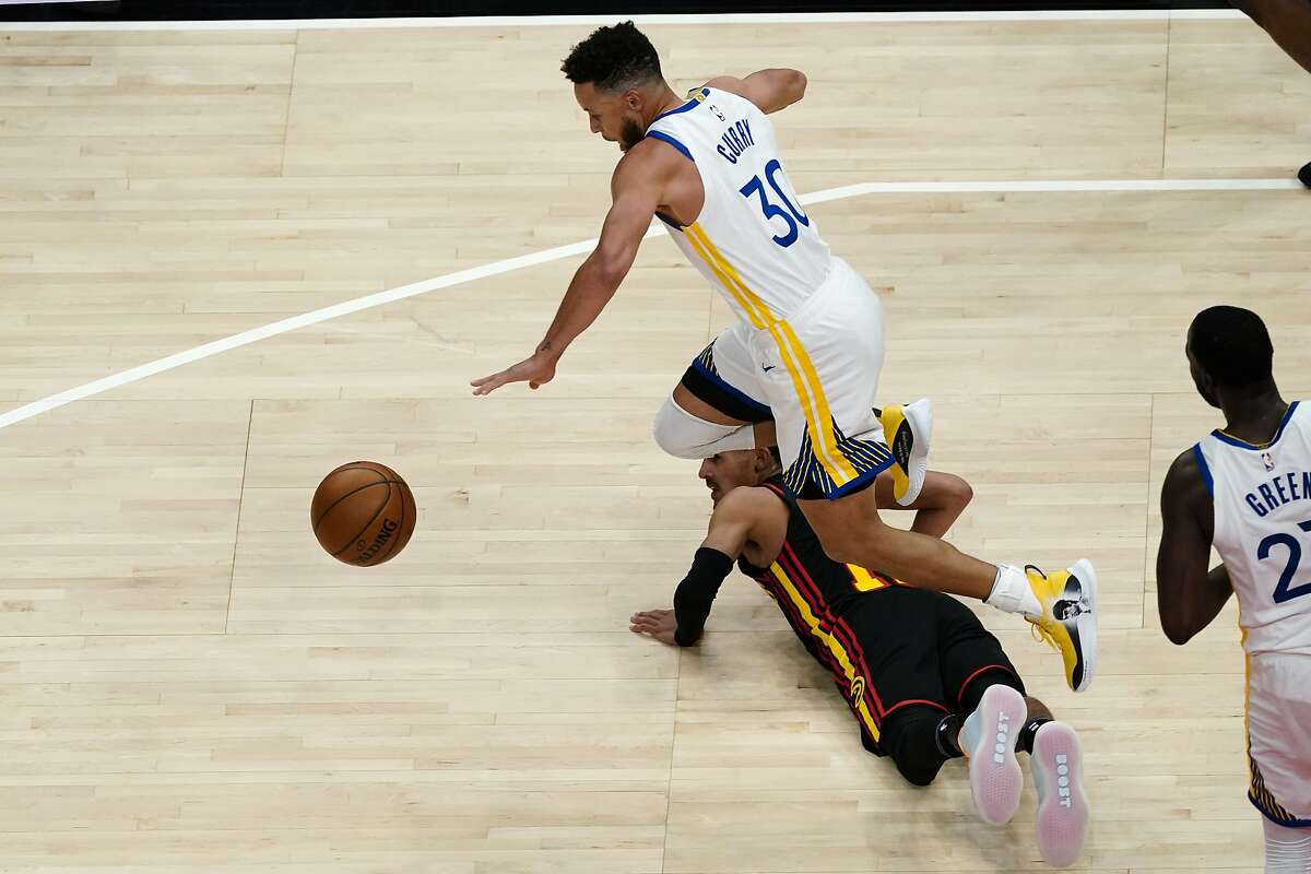 Warriors guard Stephen Curry takes a low hurdle Sunday over Hawks guard Trae Young in Atlanta's home victory Sunday. Curry led the Warriors with 37 points.