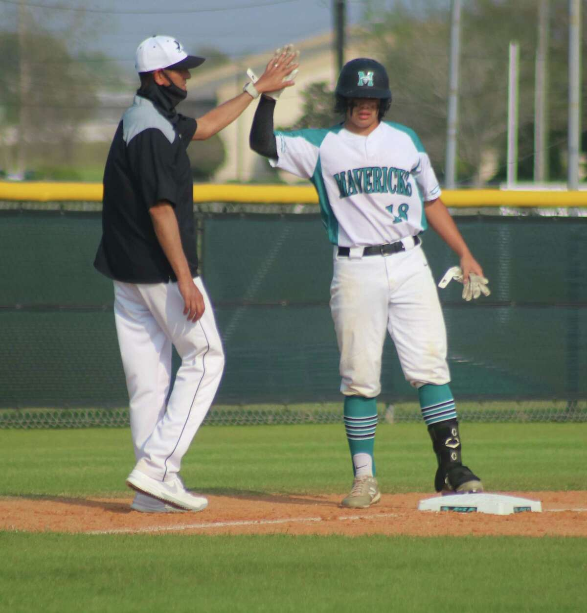 Pasadena Memorial head coach Terry Garza greets Francisco Chavez at third base after clouting a well-hit ball in a district game versus Rayburn. The Mavs will hit the meat of April's action with a four-game winning streak.