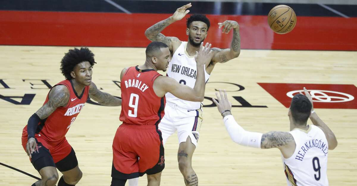New Orleans Pelicans guard Nickeil Alexander-Walker (6) passes the ball to center Willy Hernangomez (9) over Houston Rockets guard Avery Bradley (9) during the first half of an NBA basketball game at Toyota Center, Sunday, April 4, 2021.