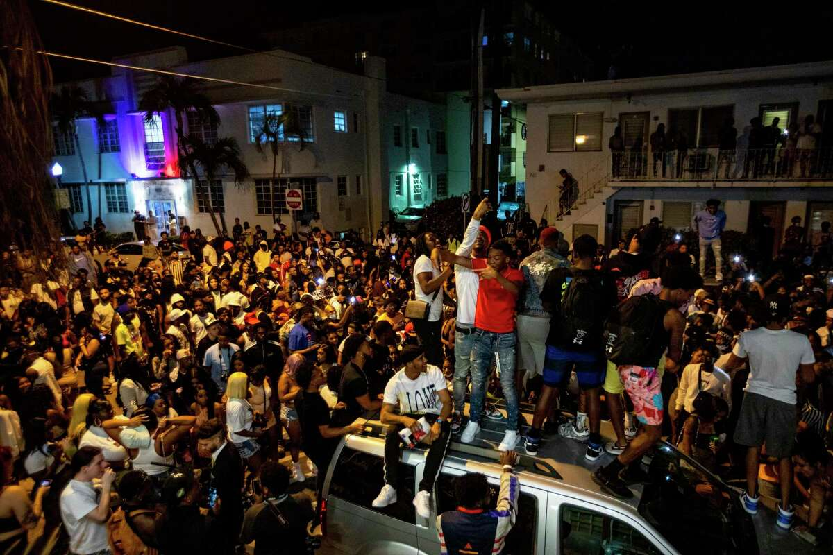 Crowds defiantly gather in the street while a speaker blasts music an hour past curfew in Miami Beach, Florida, on Sunday, March 21, 2021. An 8 p.m. curfew has been extended in Miami Beach after law enforcement worked to contain unruly crowds of spring break tourists.