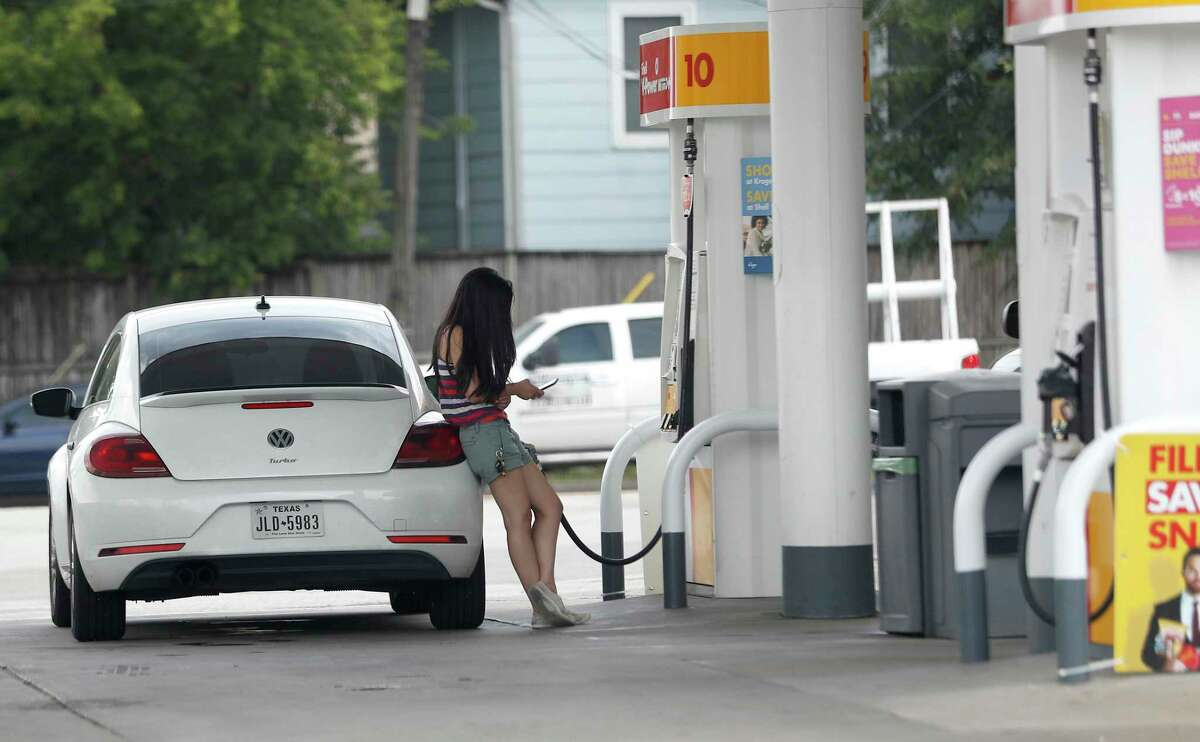 A woman pumps gas at a Bellaire area gas station, Tuesday, June 30, 2020, in Houston. U.S. energy consumption in 2020 plunged by the largest margin since historical records dating back to 1949 as the global pandemic crushed demand for crude and petroleum products such as gasoline and jet fuel.