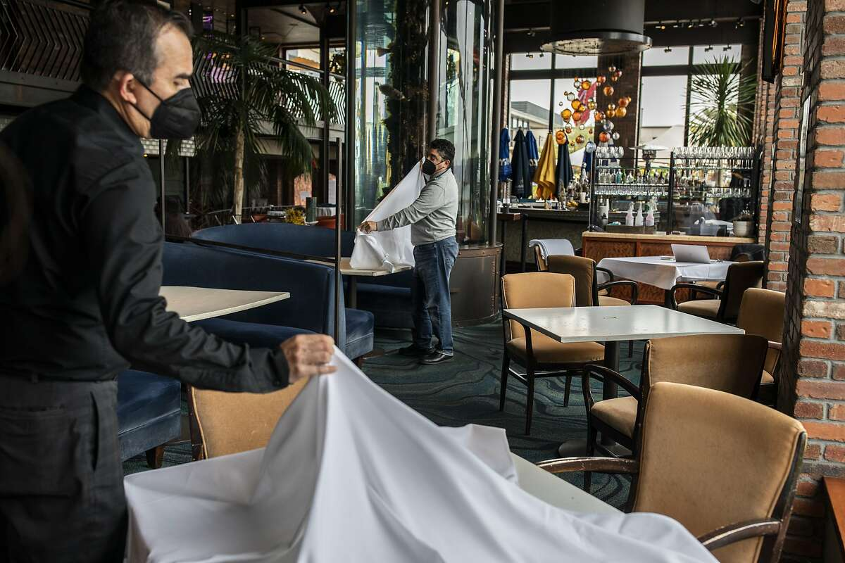 From left: Ricardo Torres and Rich Troiani put tablecloths over tables at Waterbar, Tuesday, March 2, 2021, in San Francisco, Calif. California will retire its color-coded pandemic blueprint on June 15 and allow almost all sectors of the economy, in all 58 counties, to reopen at or near full capacity, state officials said Tuesday.