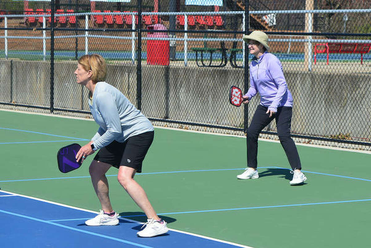 Team members Judy Kulp, foreground, and Ann Kuebrich prepare to return a volley in the Inaugural Gherkin Tournament to open the Riverbend Pickleball season Saturday at Gordon Moore Park in Alton.