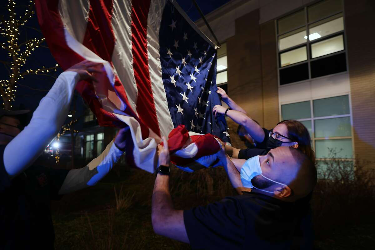 An American flag is raised as firefighters, medical workers, first responders and members of the public gather in front of a hospital in Mount Kisco, N.Y., on March 11, 2021, to mark the one-year anniversary of the first Covid-19 patient admission there.