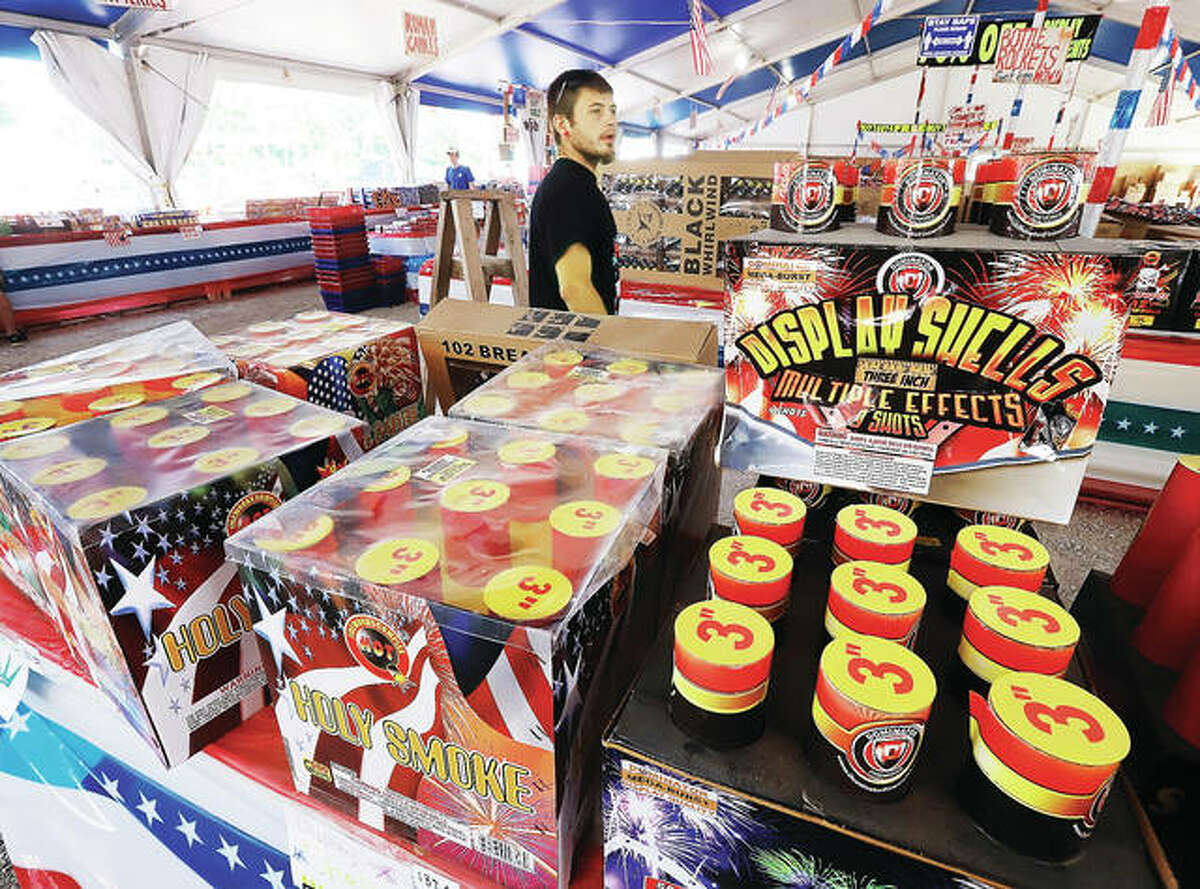 """In this July 2020 photo, a man shops with his family in the large shell section of a fireworks tent behind the Gas Mart at U.S. 67 and Missouri Highway 94 in West Alton, Missouri. Illinois lawmakers are considering a bill to allow firework """"fountains,"""" a show-in-a-box that can unleash multicolored sparks, whizzing streaks and sharp reports. Now legally sold in Missouri, opponents say the fountains will produce more fireworks-related injuries."""