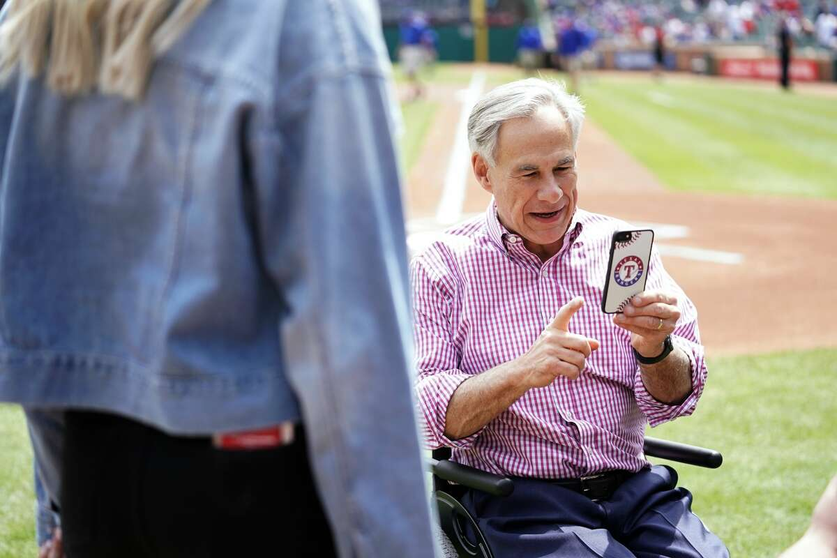 ARLINGTON, TX - MARCH 28: Texas Governor Greg Abbott uses his phone before the game between the Chicago Cubs and the Texas Rangers at Globe Life Park in Arlington on Thursday, March 28, 2019 in Arlington, Texas. (Photo by Cooper Neill/MLB via Getty Images)