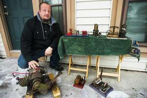 Brandon Davis poses for a portrait with his collection of scale model steam engines Thursday, Feb. 18, 2021 outside of his home in Midland. (Katy Kildee/kkildee@mdn.net)