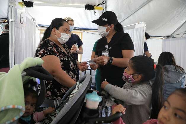 Nurse Angelica Juarez (right) provides vaccination information to Gladys Sonchonchex as she visits the Southeast Health Center vaccination tent in San Francisco with her three children. Photo: Lea Suzuki / The Chronicle