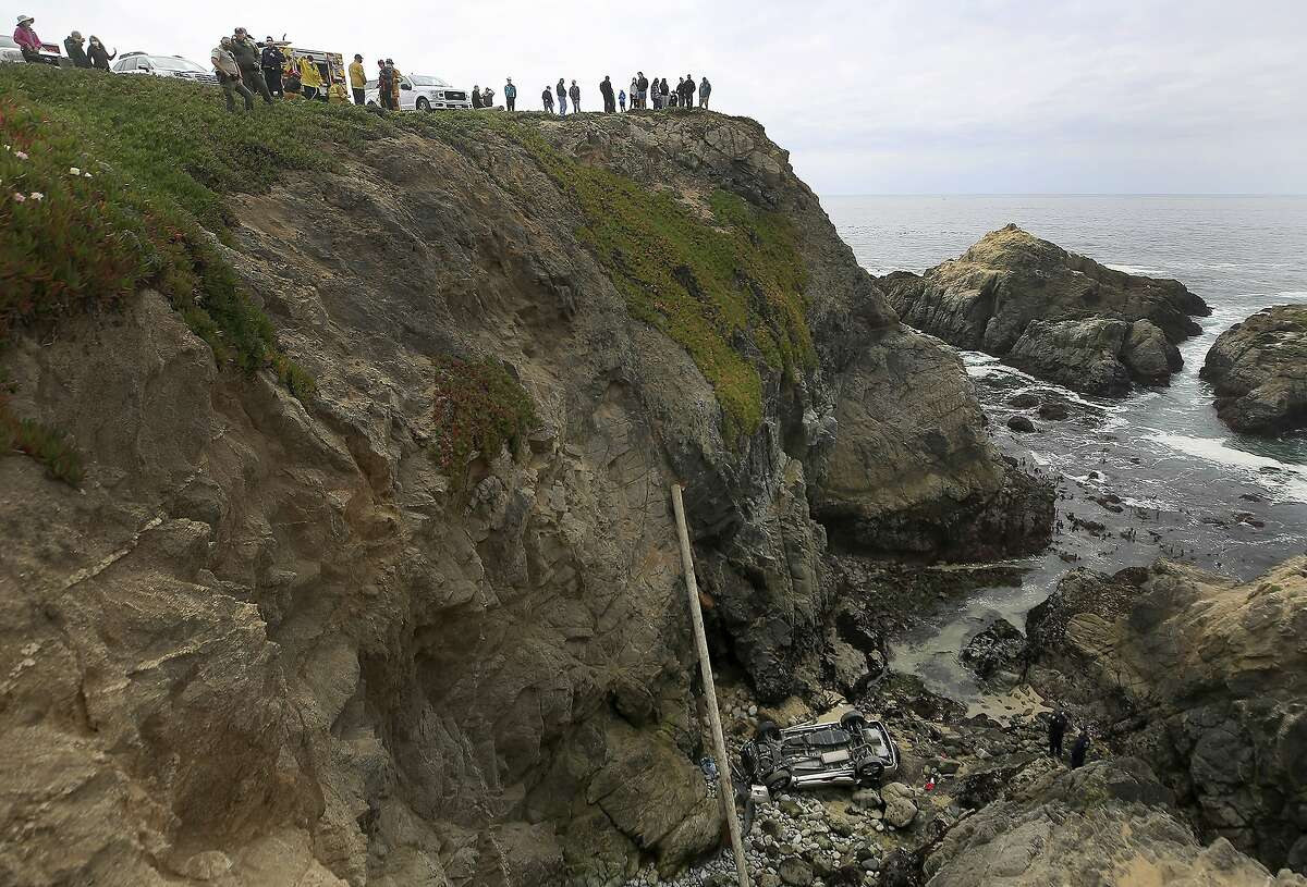 Bodega Bay firefighters work to secure the scene of a crash after a vehicle plummeted from the Bodega Head parking lot in Bodega Bay, Calif., through a wood barrier, left, landing upside down 100 feet to the rocky shoreline, killing Maria Teixeira and Elizabeth Correia, both of Dublin Saturday, April 3, 2021.