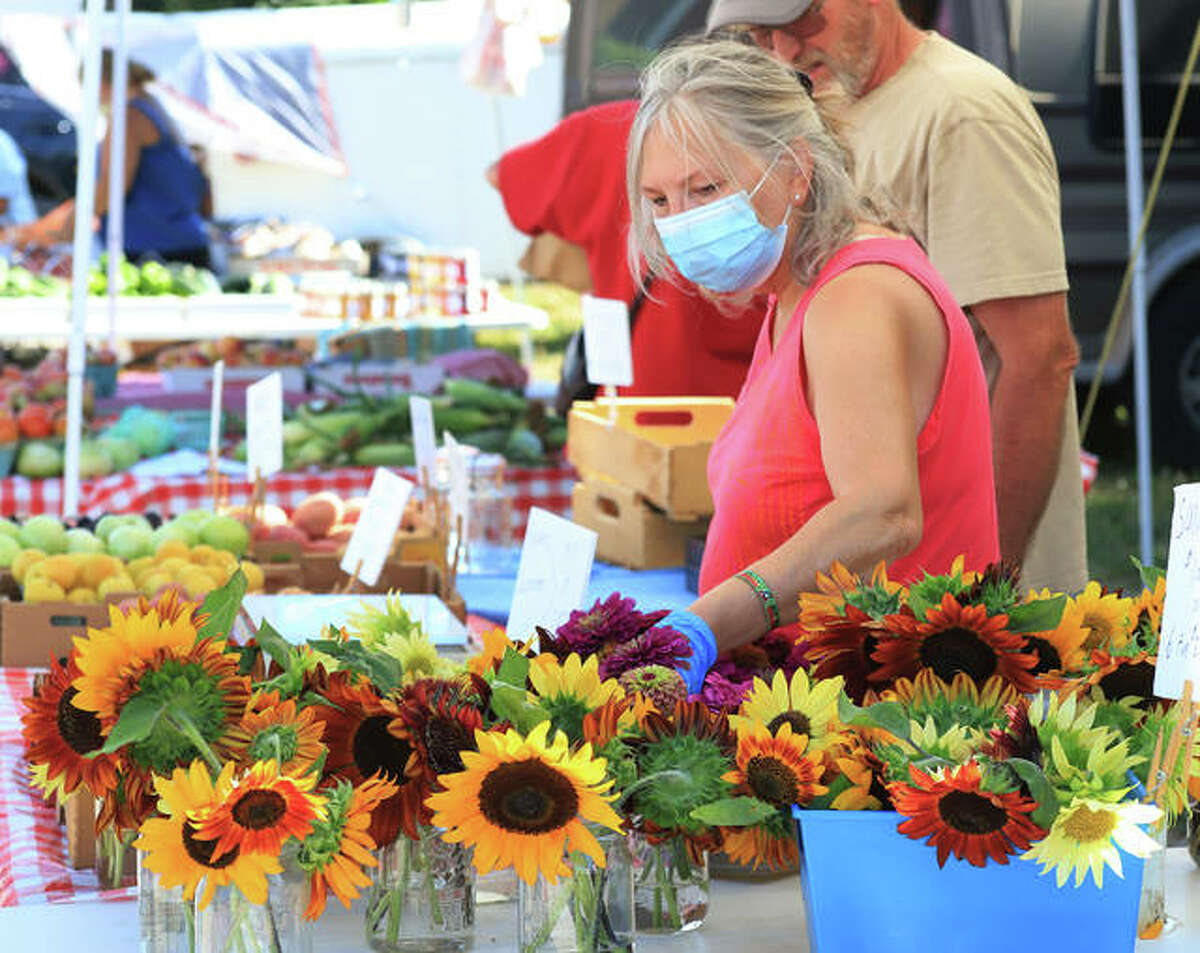 In this July 2020 photo, participants look over offerings at the Alton Farmers' and Artisans' Market. On Saturday, May 8, the market is scheduled to resume. The event will be offered 8 a.m. to noon on Saturdays through Oct. 16 at the corner of Landmarks Boulevard and Henry Street in Alton.