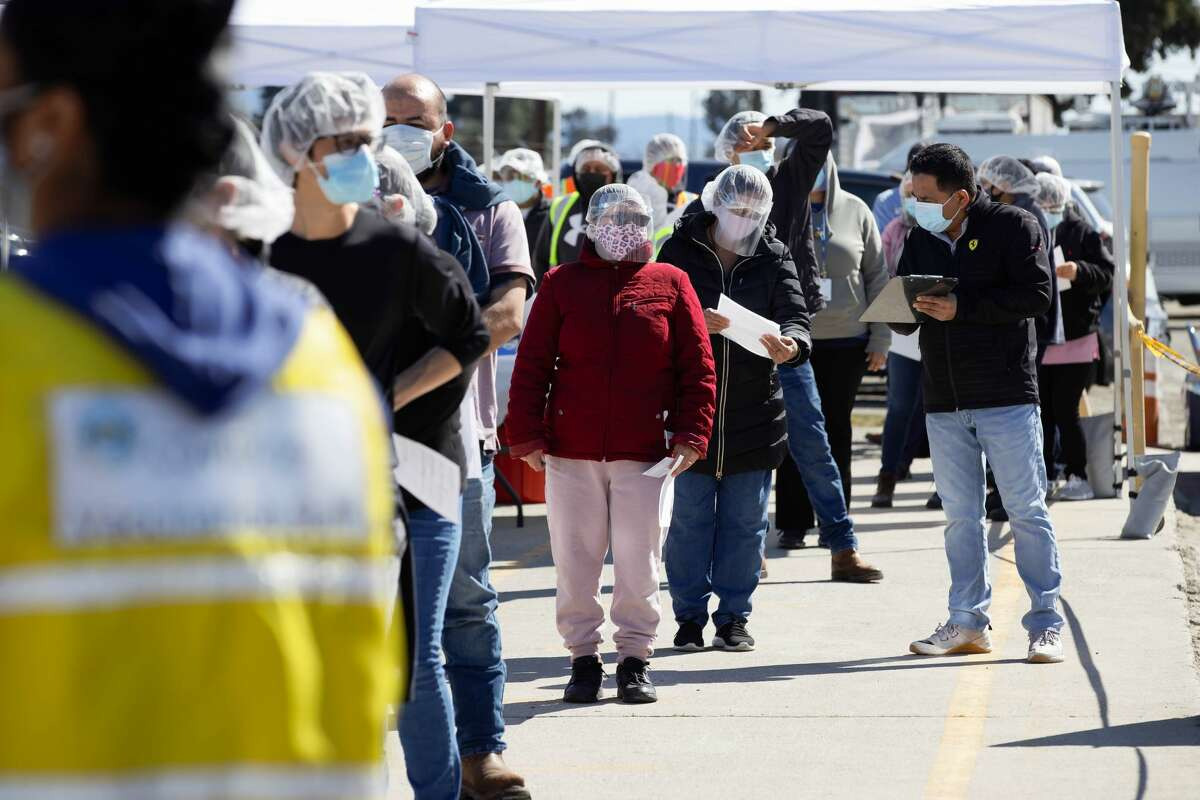 Workers wait in line to receive their vaccine at Monterey Mushrooms in Morgan Hill, Calif., on Sunday, Feb. 28, 2021.