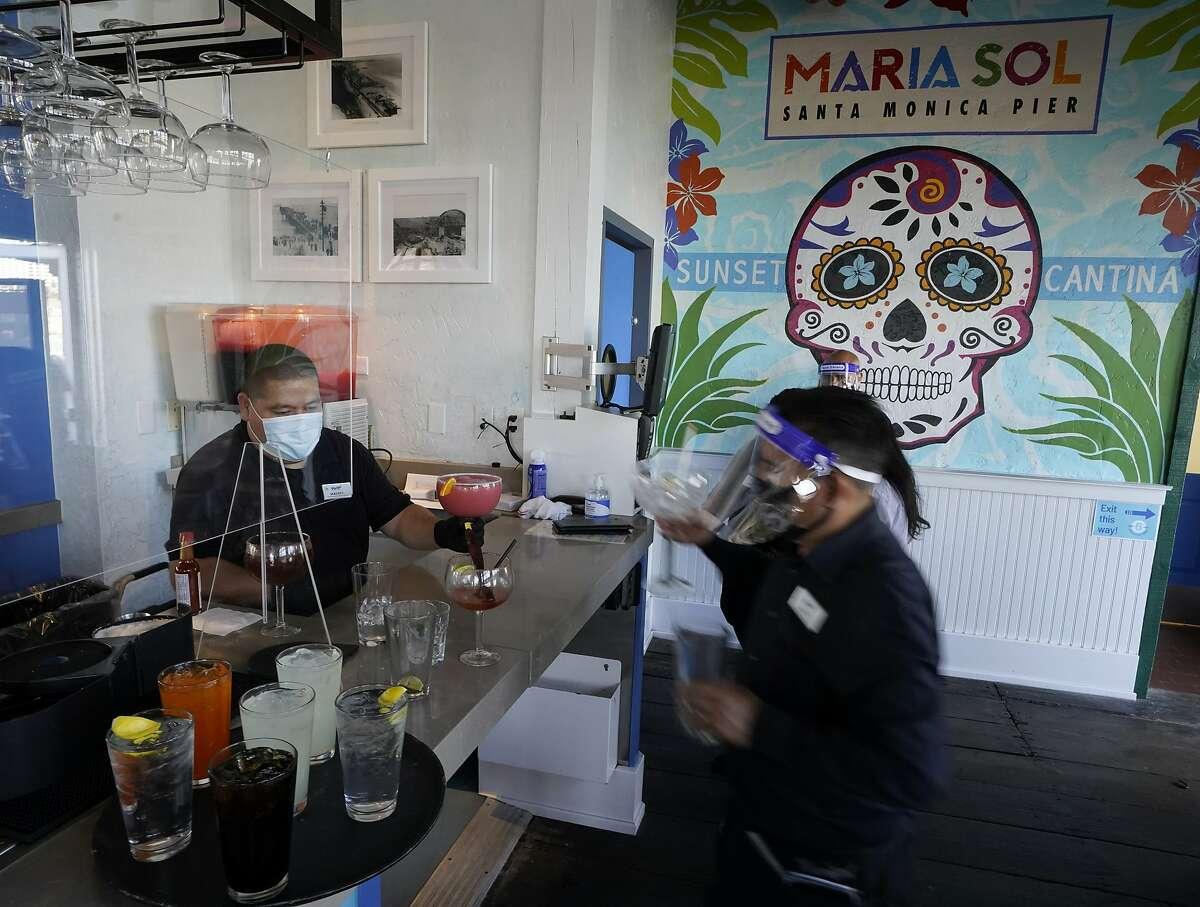 Barman Gustavo prepares drinks behind plexiglass protective wall at Maria Sol on the Santa Monica Pier as the pier restaurant opens for indoors service in Santa Monica, Calif., Wednesday, March 31, 2021. Los Angeles County can reopen even more businesses while expanding how many people are allowed to dine indoors or catch a movie, California public health officials announced Tuesday, March 30, 2021. The county of 10 million people was one of several that moved into the state's orange tier, which is the second-least restrictive of California's four-tier system. (AP Photo/Damian Dovarganes)