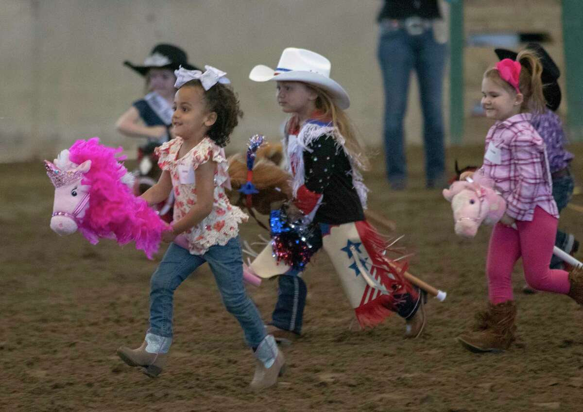 Stick horse racers run across the arena during the Youth Events at the Montgomery County Fair & Rodeo on Friday, March 29, 2019, in Conroe. The fair kicked off Friday and will end Sunday, April 7.