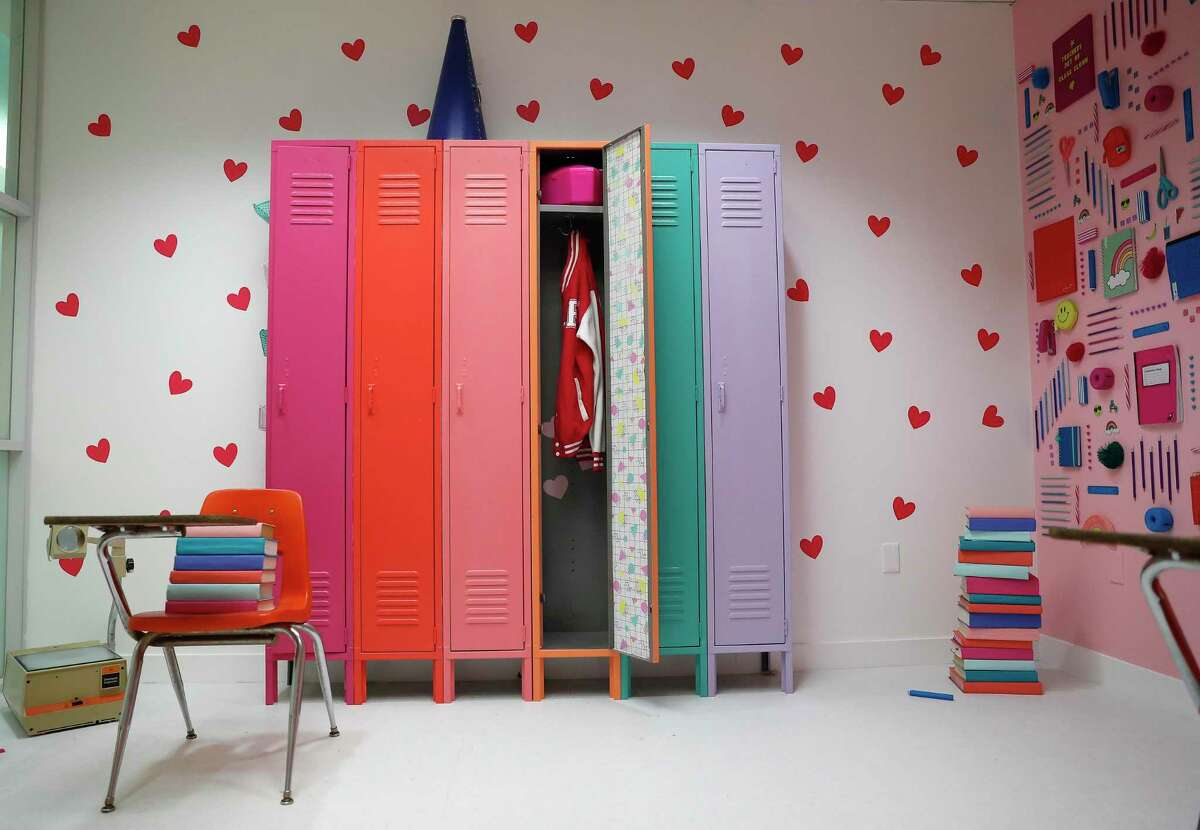 """Colorful lockers with things inside on one wall in the """"school room,"""" one of several FOMO factory's themed rooms in the Galleria mall, in Houston, May 16, 2019. In a suit, Founder Rachel Youens' parents said she """"believed that Gallery Furniture ... would get away with stealing her ideas, her dreams and that her business would inevitably fail as a result."""""""