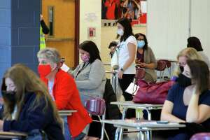 Teachers and staff from all over Monroe's school system wait the mandatory 15 minutes to monitor for reactions after receiving the COVID-19 vaccine during a closed vaccine clinic for Monroe school staff at Masuk High School in Monroe, Conn., on Wednesday Mar. 3, 2021.