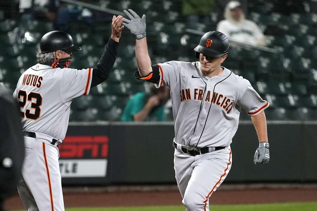 San Francisco Giants' Alex Dickerson, right, is congratulated by third base coach Ron Woltus after Dickerson's solo home run against the Seattle Mariners during the ninth inning of a baseball game Thursday, April 1, 2021, in Seattle. (AP Photo/Elaine Thompson)